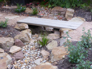 Blackburn dry creek bed with timber bridge and rocks.