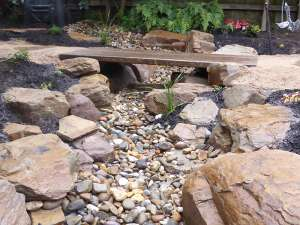 Ornamental dry creek bed with timber bridge